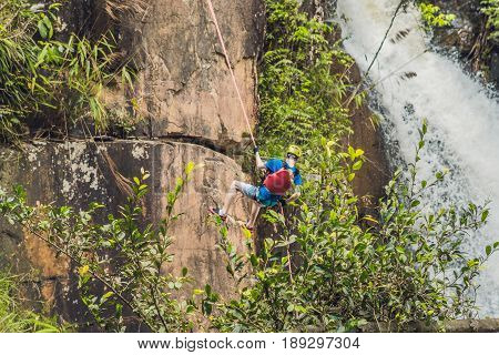 Climber in the background of beautiful cascading Datanla waterfall In the mountain town Dalat Vietnam.