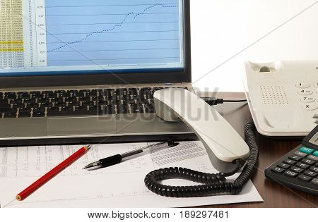 Laptop computer telephone receiver pen pencil and papers