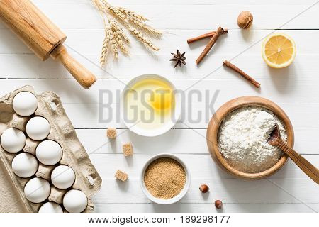 Baking ingredients on white wooden table. Eggs, brown sugar, white flour, wheat ears, spices, nuts and lemon on white wooden background. Table top view