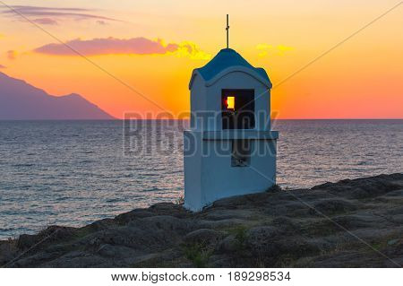 Small greek chapel and mount Athos at sunrise or sunset and sea panorama in Greece