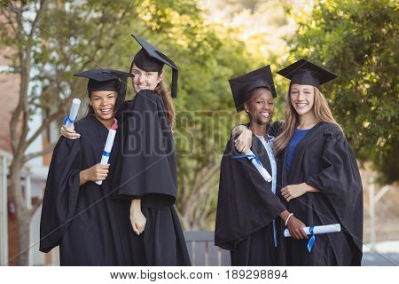 Portrait of graduate school kids standing with degree scroll in campus at school