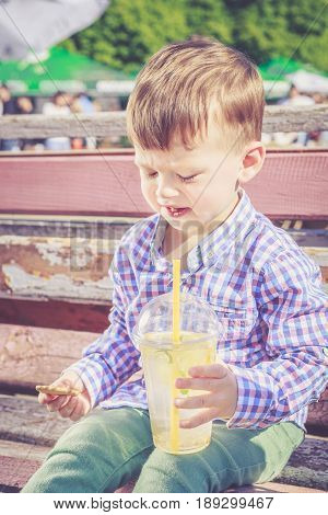 Two years old boy frowned when he tasted a bitter lemon seed while drinking lemonade. Poor quality food street food concept