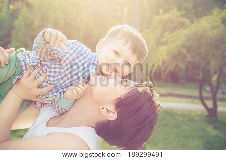 Happy mother playing with her toddler son in the park at sunset. Mothers day celebration concept