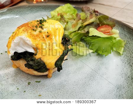 Close-up Egg Benedict with Spinach Served with Salad