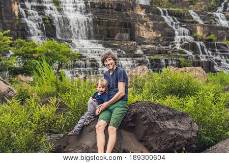 Father And Son Hikers, Tourists On The Background Of Amazing Pongour Waterfall Is Famous And Most Be