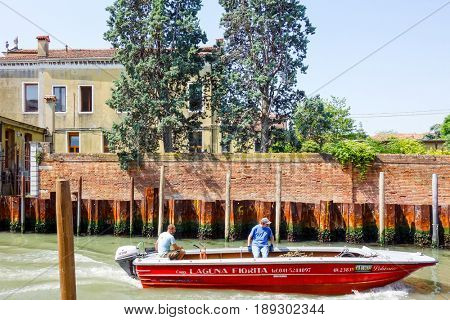 VENICE,ITALY-May 18, 2017. Tourists on water street with Gondola in Venice. its entirety is listed as a World Heritage Site, along with its lagoon