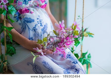 Pregnant woman surrounded by spring flowers sitting by the window