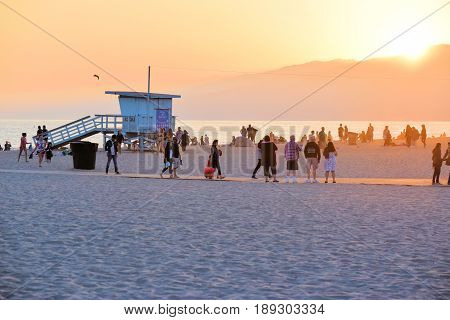 June 2, 2017 in Santa Monica, CA:  People resting and watching the sunset over the Santa Monica Mountains and Pacific Ocean at Santa Monica Beach where people can enjoy leisure activities on the beach taken in Santa Monica, CA