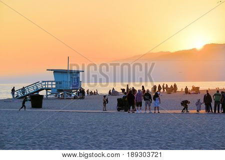 June 1, 2017 in Santa Monica, CA:  People relaxing and watching the sunset over the Pacific Ocean and the Santa Monica Mountains taken at Santa Monica Beach, CA where people can swim and relax on the sand