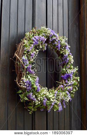 Grapevine floral wreath with purple flowers and greenery, hanging on black painted wooden door with thin panels