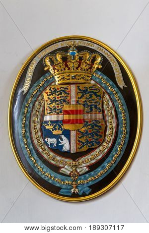 HILLEROD, DENMARK - JUNE 30, 2016: This is coat of arms of the reigning queen Margaret II in the interior of the Frederiksborg Castle.