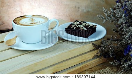 Cappuccino coffee and sweet chocolate brownies cake. A cup of latte, cappuccino or espresso coffee with milk put on a wood table with dark roasting coffee beans. Latte art by milk on top with flowers.