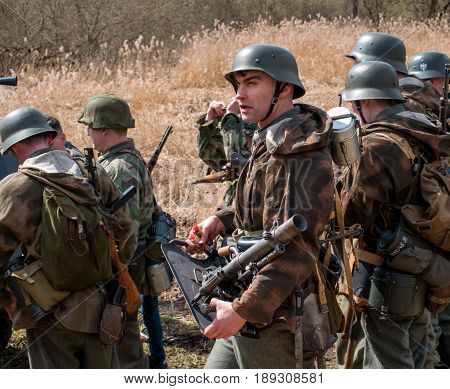 Gatchina, Russia - May 7, 2017: Historical reconstruction of the battles of World War II. The participants in the form of German soldiers preparing for battle.