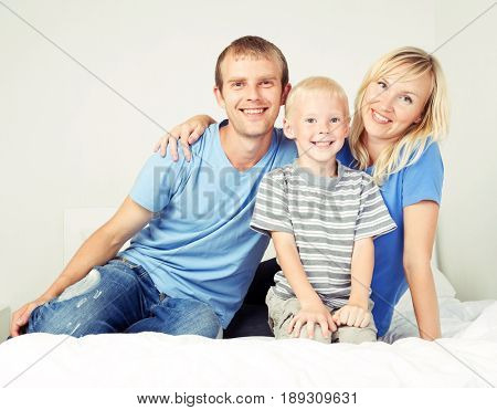 happy family: father, mother and son  relaxing in bed at home