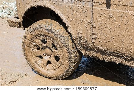 Dirty wheel of an off-road car after driving in the rain