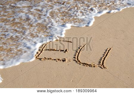 The word EU written in the sand and being washed away by the sea. Concept for failure of the European Union.