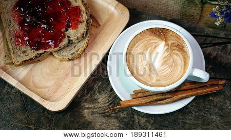 A cup of latte or cappuccino coffee with milk on a wood table with roasting coffee beans and toast. Aroma and flavor coffee beverage. Morning breakfast with coffee. Latte art created by pouring steamed milk.