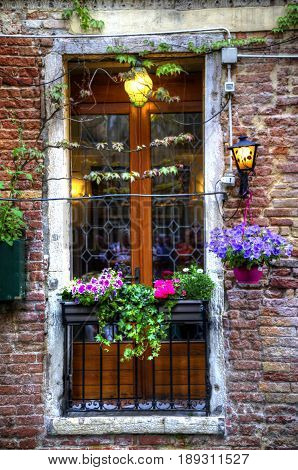 Detail of a window in Venice with flowers and lights.