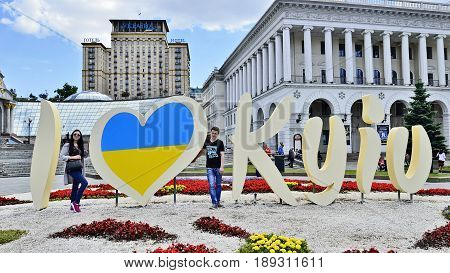 KYIV UKRAINE - CIRCA MAY 2017: Celebration 1535-th Day of Kyiv. Young pair stay near stylized banner I LOVE KYIV for image taking