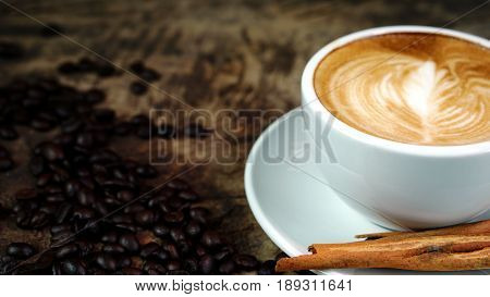 A cup of latte or cappuccino coffee with milk on a wood table with roasting coffee beans. Aroma and flavor coffee beverage. Morning breakfast with coffee. Latte art created by pouring steamed milk.