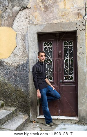 Young handsome man standing near the door at the dingy walls.