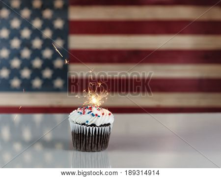 Chocolate cupcake and exploding sparkler with rustic wooden United States Flag in background. July 4th holiday concept