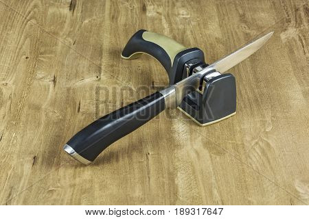 A metal knife with a plastic handle and a sharpener on a wooden surface