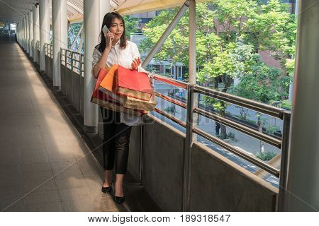Beautiful young woman holding shopping bags and talking on the phone In the link.