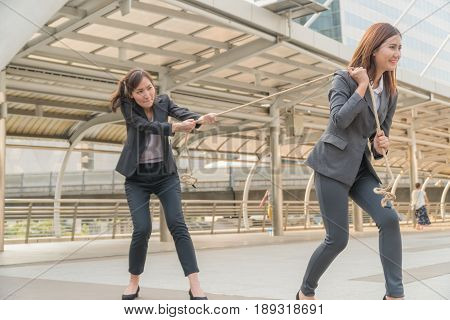 Two Beautiful woman pulling a rope with in modern city.