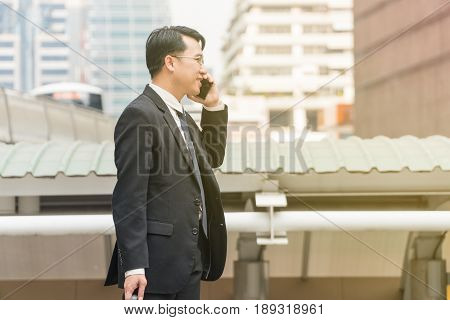 Asian middle-aged businessman talking Smart phone while traveling in modern city.