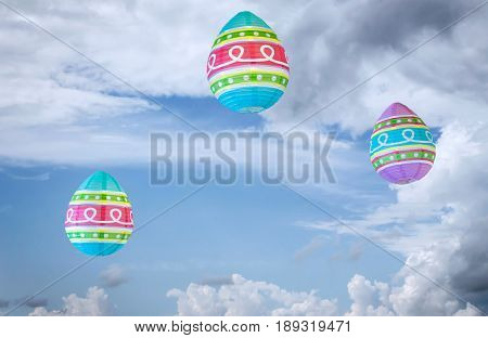 horizontal image of colourful paper lanterns floating in a blue sky with white puffy clouds.