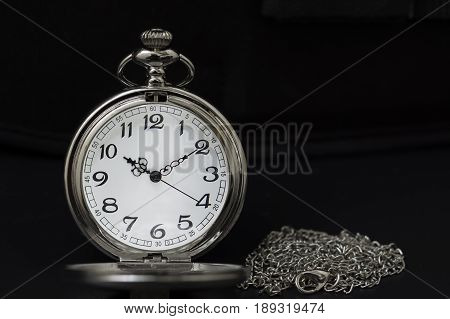 pocket watch with a black keyboard background.