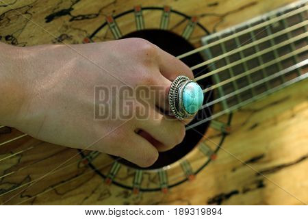 Musician's hand strumming an acoustic guitar with turquoise ring.