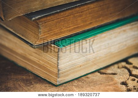 Three ancient books are placed on wooden table.
