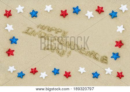 Independence USA background with white red and blue stars on the sandy beach near ocean