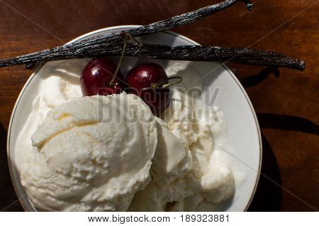Beautiful Vanilla Ice cream scoop on plate with red Cherry and Vanilla bean pods gourmet food background photography conceptual summer treats