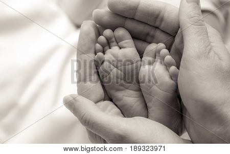 hands holding babies feet the shot is  monochromatic