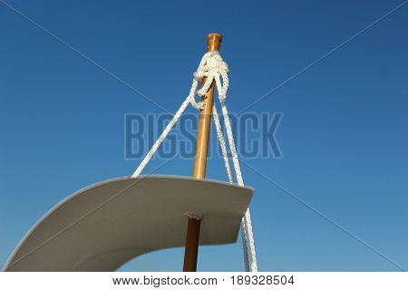 The top of the sail on a makeshift ship made of cardboard against the blue sky