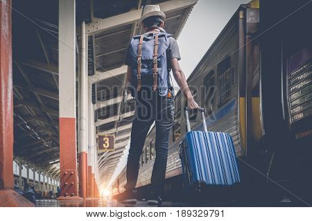 Enjoying Travel. Young Traveler Walking With Suitcase And Classic Train At Railway Platform. Alone T