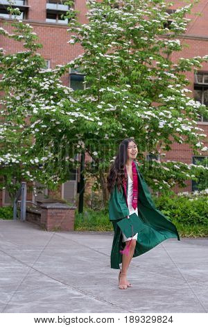 EUGENE, OR - MAY 22, 2017: College senior having fun during graduation photos on campus at the University of Oregon in Eugene.