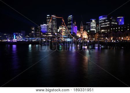 Beautiful scene of colorful Sydney city skyline by night at Campbell's Cove during Vivid Sydney Lights Festival. Free annual outdoor event of light music and ideas.