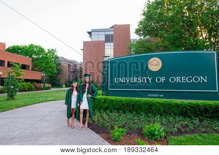EUGENE, OR - MAY 22, 2017: Two females pose for graduation photos in front of the main entrance sign on campus at the University of Oregon in Eugene.