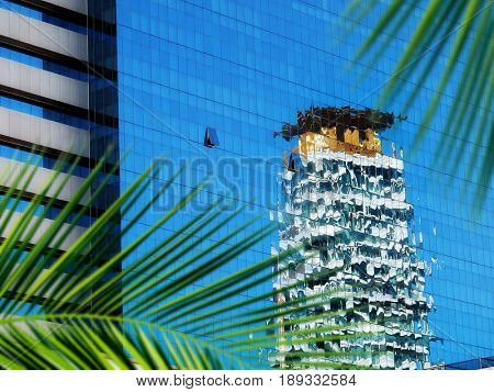 close up architectural detail from tall glass building and palm tree in Thailand