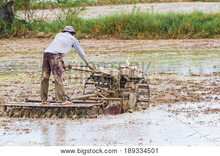 The farmer is plowed with a tractor in his farm and the birds are eating fish around.