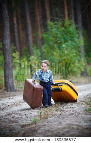 A little boy is pulling two huge suitcases along a deserted forest road - East or West home is best.