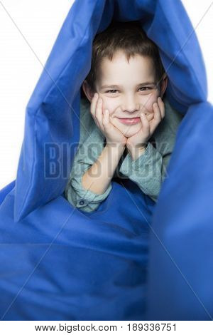 Boy with his head in his hands smiling sitting in a blue sleeping bag