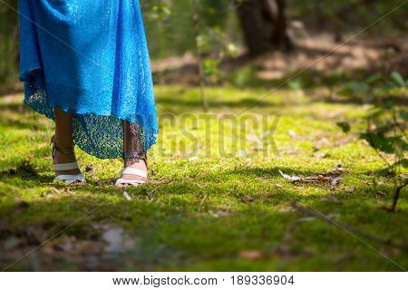 A girl in a blue lace dress and shoes lost her way in the forest. Her feet stand on the moss in the sunshine