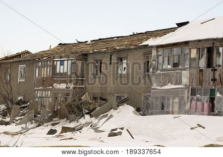 Old two-storied destroyed house in winter with snow around. Poverty and misery, North