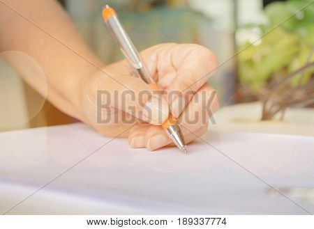 university students hand testing doing examination with blurred abstract background in exam classroom educational college