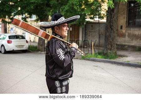 Mexican musician playing guitar on city street